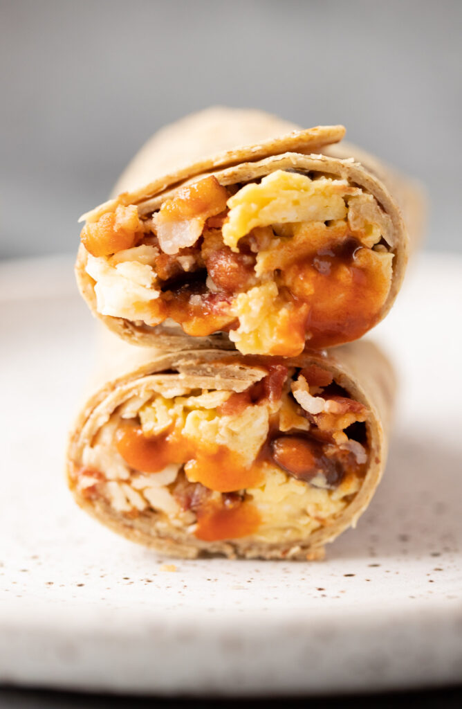 A close up of the best healthy breakfast burritos cut in half and stacked on top of one another.
