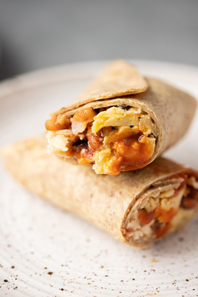 A close up of a healthy breakfast burrito on a white plate cut in half