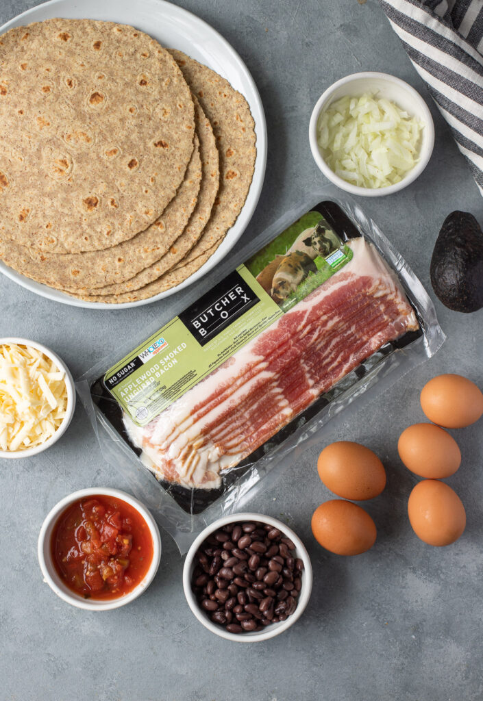 Ingredients for this Healthy Breakfast Burrito in small whit ebowls on a grey background