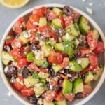 A bowl of traditional greek salad on a grey background with ingredients all around it