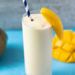 A mango smoothie on a blue background with mangos off to the side and a blue paper straw