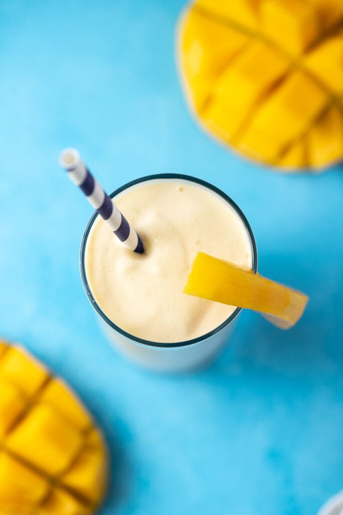 An overhead shot of a mango smoothie recipe on a bright blue background with sliced mangoes off to the sides.